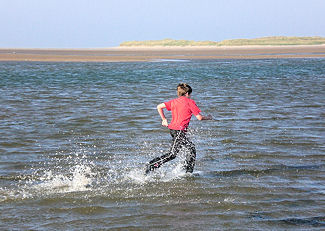 running through the sea at holy island causeway